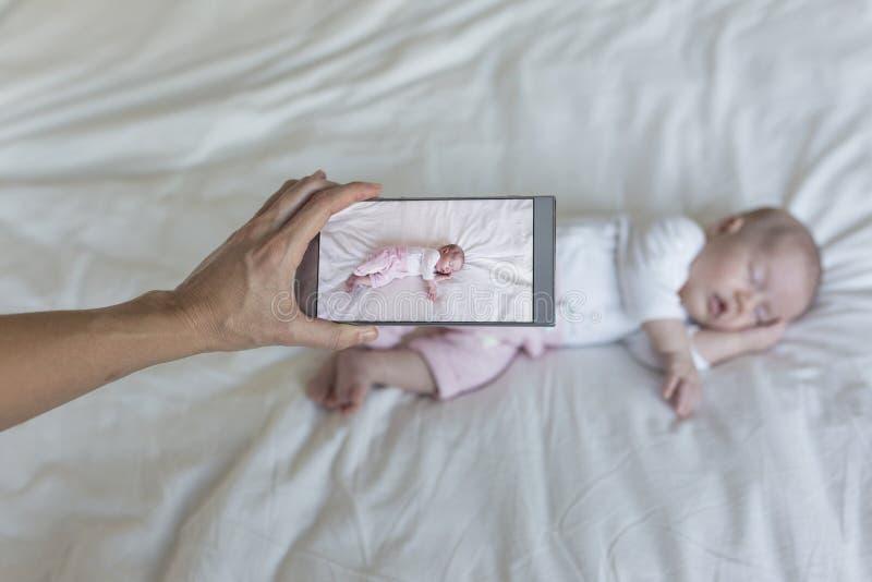 拍她的女婴的照片母亲睡觉在床上 家庭和爱概念 图库摄影