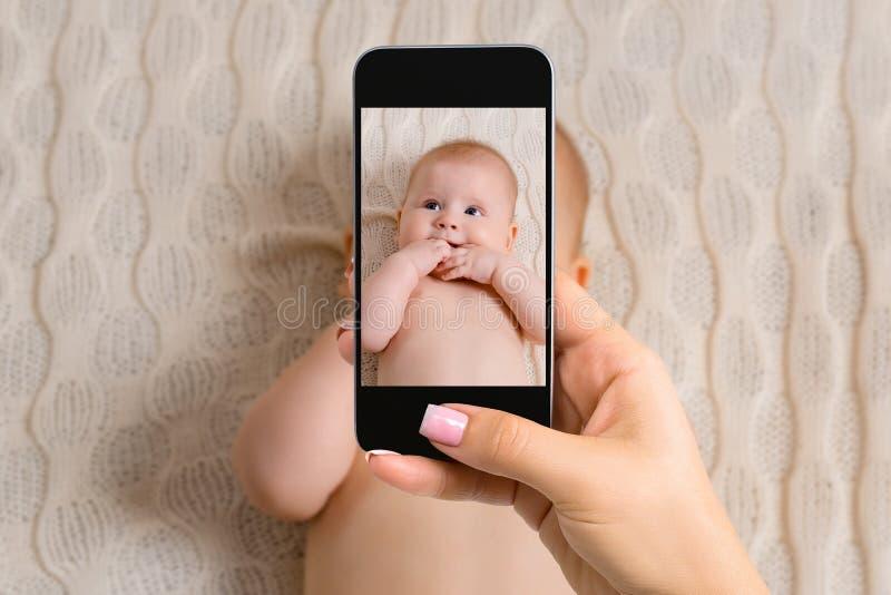 拍她的小儿床的女婴的照片愉快的母亲有巧妙的电话的 图库摄影