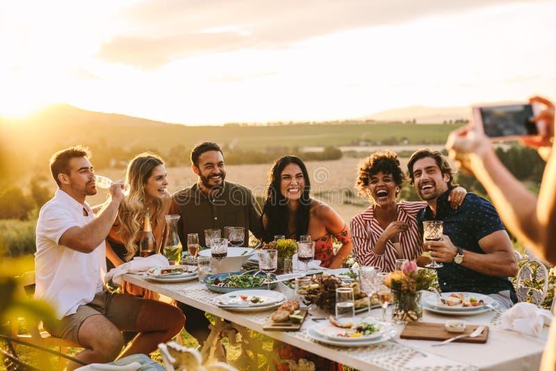 拍她的朋友的照片妇女在晚餐会 免版税库存图片