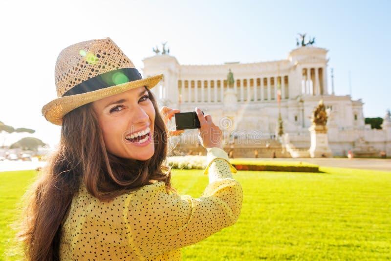 拍威尼斯广场纪念碑的照片笑的妇女 库存照片
