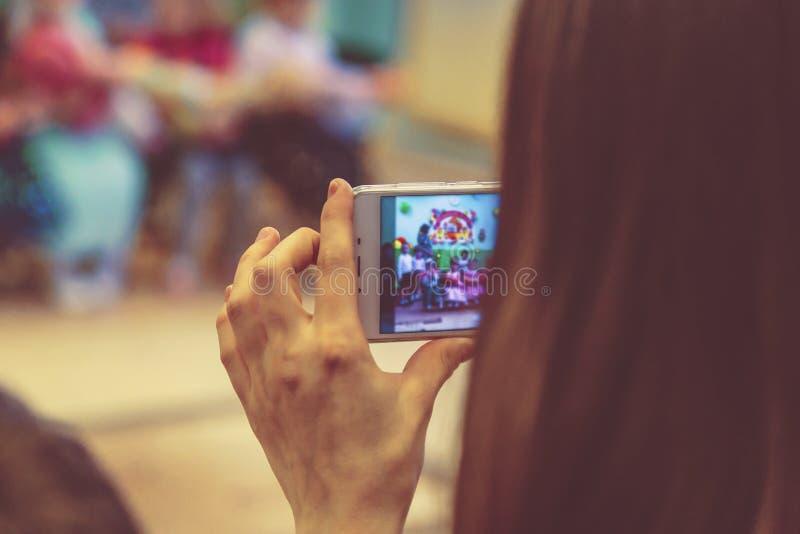 拍孩子的照片电话的妇女在幼儿园 免版税库存照片