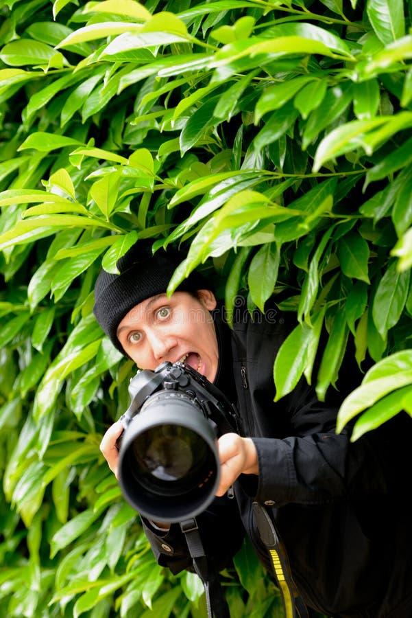 拍摄与他的dslr照相机的无固定职业的摄影师,年轻和可爱的人照片 免版税图库摄影
