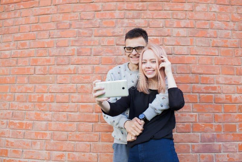 拍摄与智能手机的年轻夫妇一selfie在红砖墙壁背景  图库摄影