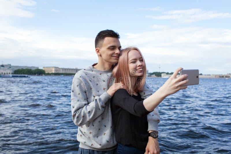 拍摄与智能手机的年轻夫妇一selfie在都市风景的背景 在圣徒的河堤防 免版税库存图片