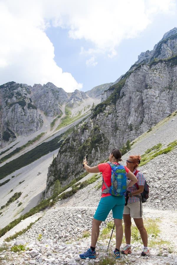 拍摄在山峰的两个俏丽的妇女远足者一selfie 免版税库存图片