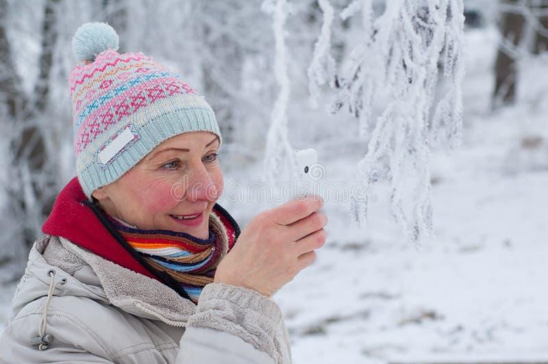 拍摄在手机的妇女在冬天公园 库存图片