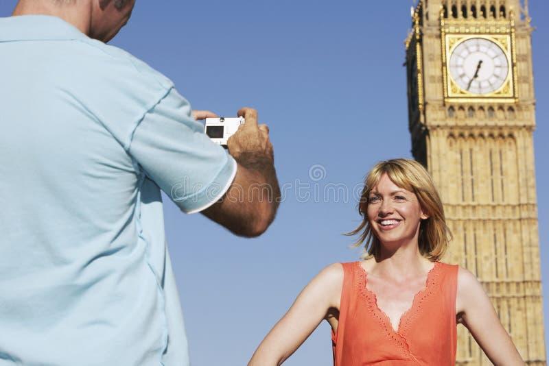 拍摄妇女的人反对大本钟塔 免版税库存照片