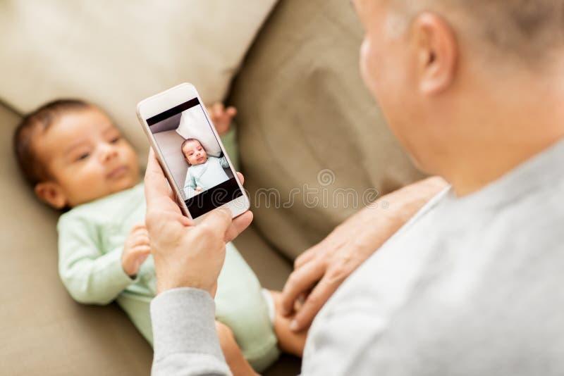 拍摄婴孩的父亲由智能手机 免版税图库摄影