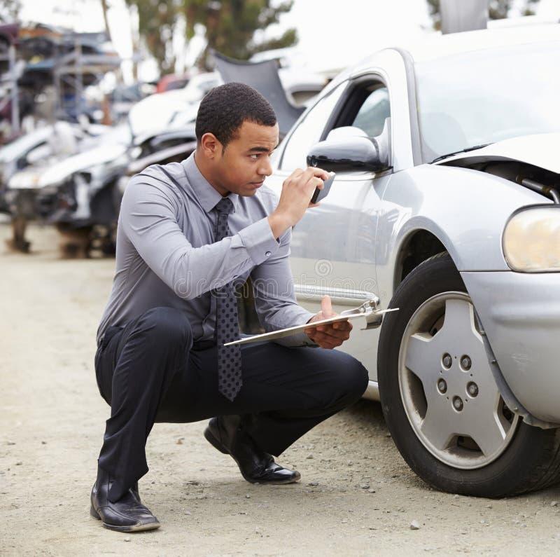 拍摄损伤的照片对汽车的保险赔偿估定员 库存图片