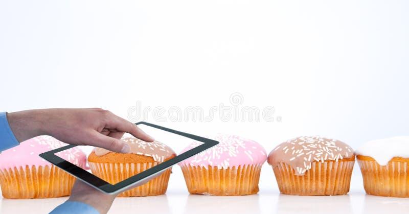 拍摄松饼的播种的手通过数字式片剂 免版税库存图片