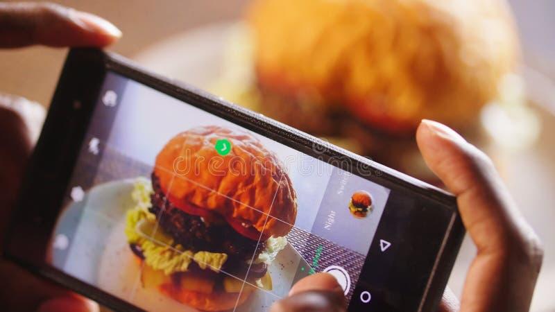 拍摄汉堡的手机 在咖啡馆桌上的汉堡包 免版税库存照片