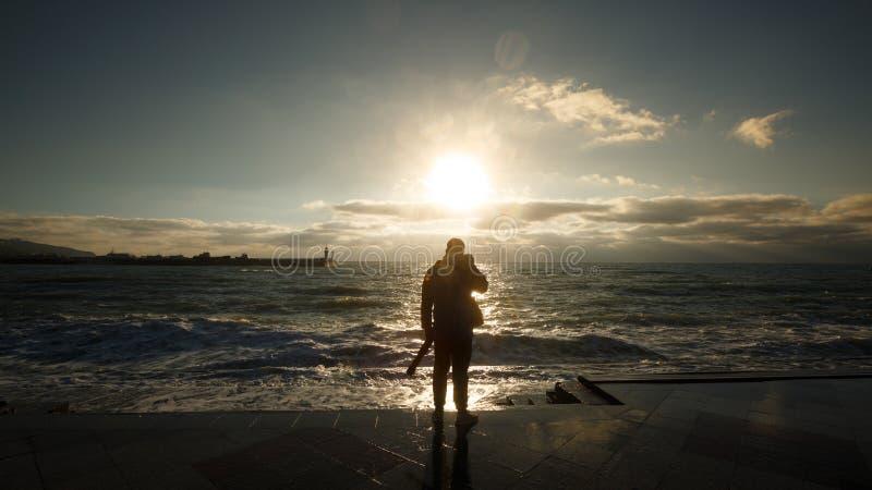 拍摄波浪的一个人的剪影 旅游摄影师射击湿堤防的风雨如磐的海 免版税库存照片