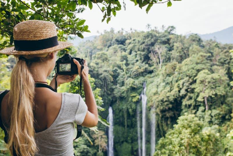 拍摄瀑布的女性游人在森林里 免版税库存图片
