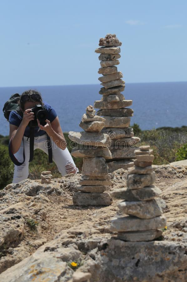 拍摄照片的女孩在石头旁边在majorca海岛的南海岸登上  免版税库存照片
