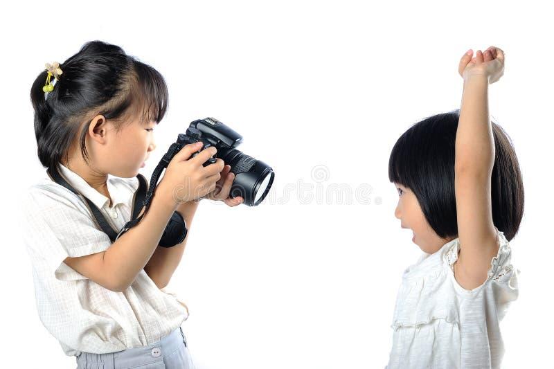 拍摄照片的彼此的亚裔矮小的兄弟姐妹孩子与 免版税图库摄影