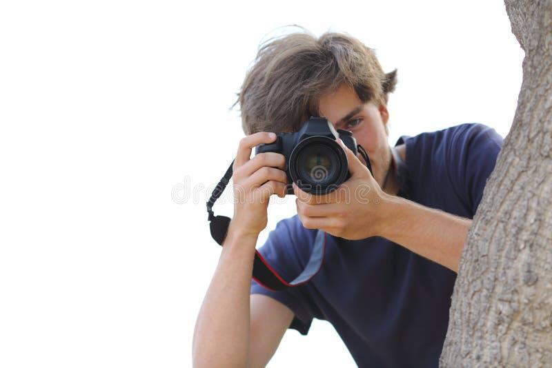 拍摄照片的无固定职业的摄影师掩藏在白色 库存照片
