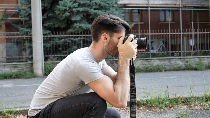 拍摄照片的英俊的年轻男性摄影师 库存图片
