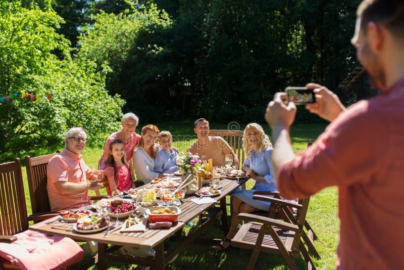 拍摄由智能手机的愉快的家庭在夏天 免版税库存图片