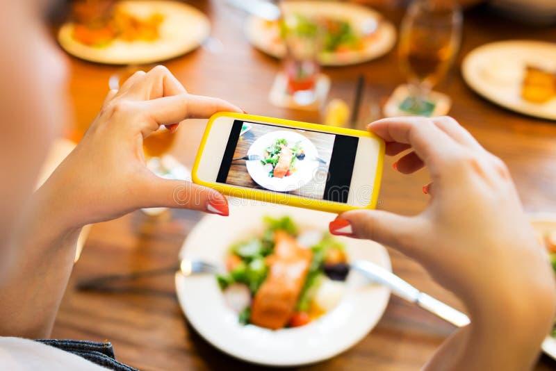 拍摄食物的手由智能手机 免版税库存照片