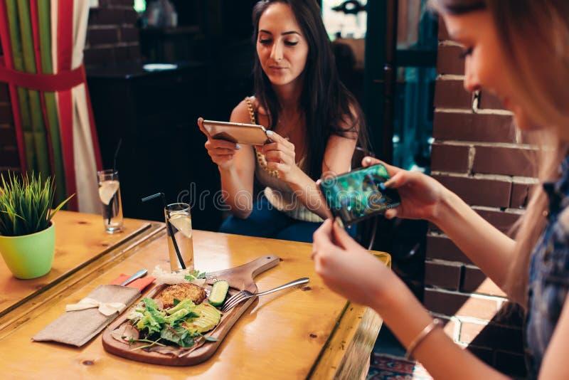 拍摄他们的与智能手机的年轻女性食物博客作者午餐在餐馆 免版税库存图片