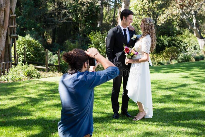 拍新婚的夫妇的照片摄影师 库存照片