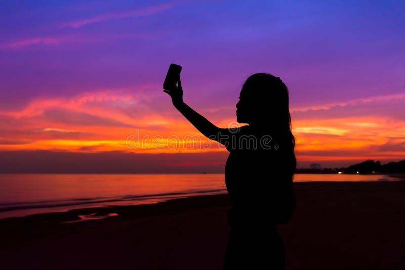 拍日落的照片与手机的妇女剪影,在 免版税库存图片
