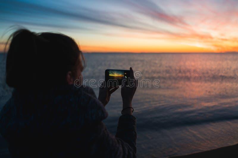 拍日落的照片的与她的智能手机的一个少妇的剪影 库存照片