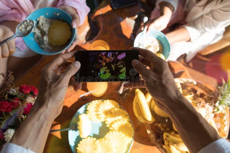 拍早餐桌的照片男性手油罐顶部角钢视图用新鲜水果和燕麦粥粥 免版税图库摄影