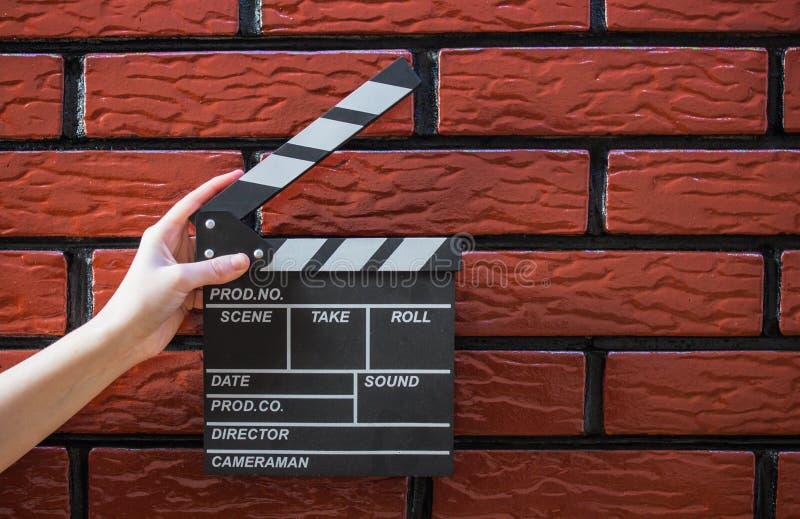 拍板板材、妇女` s手和一个电影拍板有砖的b 库存照片