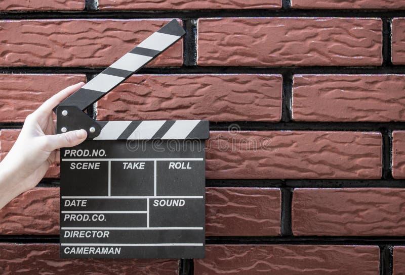 拍板板材、妇女` s手和一个电影拍板有砖的b 免版税库存图片