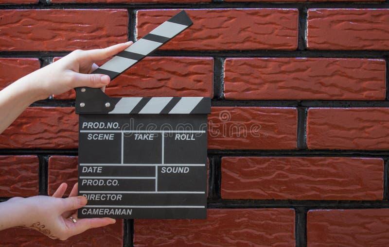 拍板板材、妇女` s手和一个电影拍板有砖的b 免版税库存照片