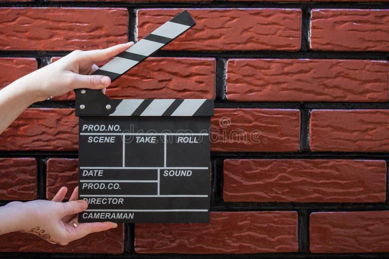 拍板板材、妇女` s手和一个电影拍板有砖的b 库存图片