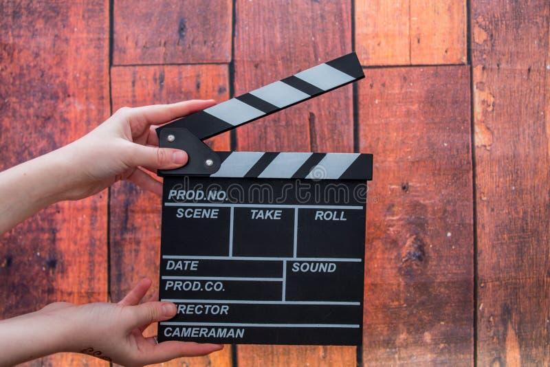 拍板板材、妇女` s手和影片拍板在一木backg 库存图片
