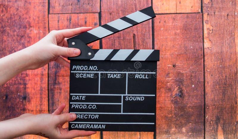 拍板板材、妇女` s手和影片拍板在一木backg 免版税库存图片