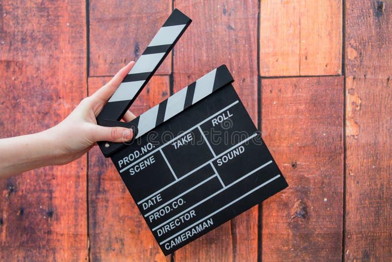 拍板板材、妇女` s手和影片拍板在一木backg 免版税图库摄影