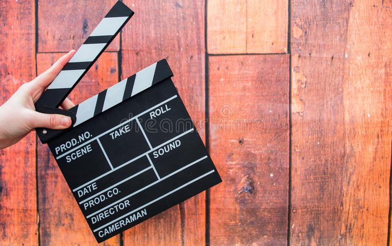 拍板板材、妇女` s手和影片拍板在一木backg 免版税库存照片
