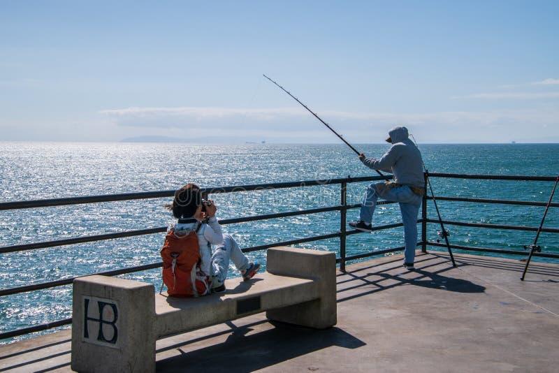 拍渔夫的照片少女钓鱼亨廷顿海滩码头的末端 免版税库存照片