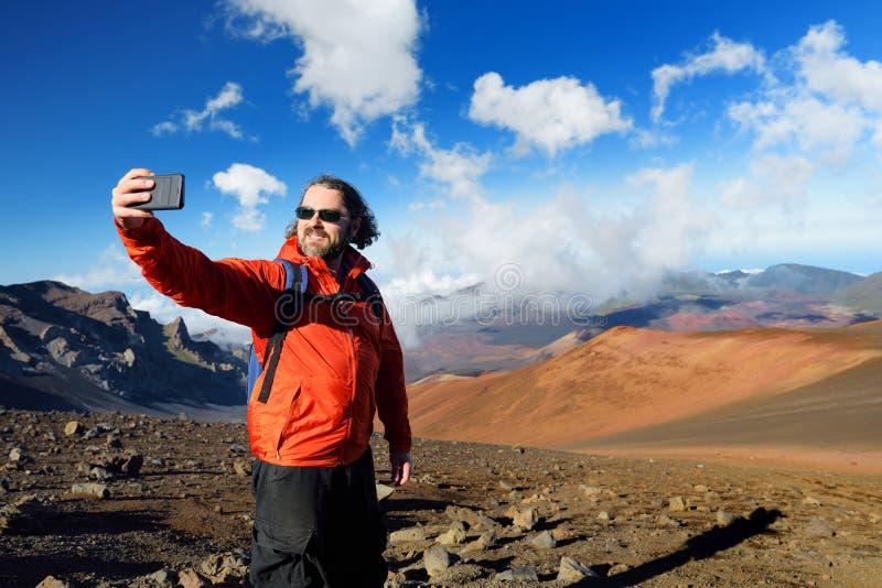拍照片他自己的游人在Haleakala在滑的沙子的火山火山口落后 毛伊,夏威夷,美国 库存照片