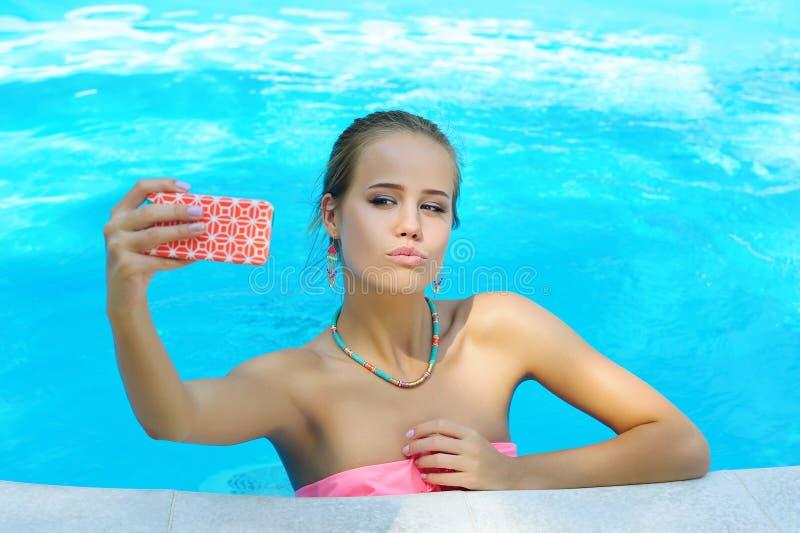 拍照片她自己的华美的少妇在水池 免版税库存照片