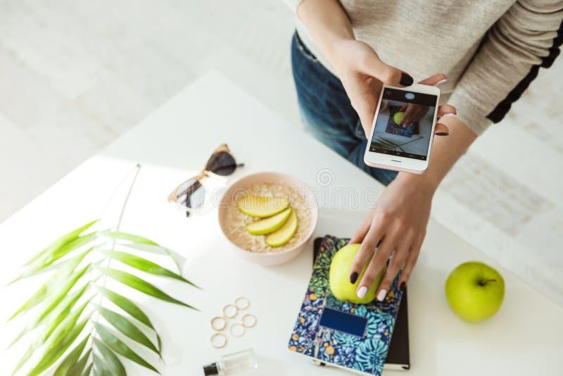 拍照片用苹果,在whie桌上的笔记本的时髦的女孩 库存照片