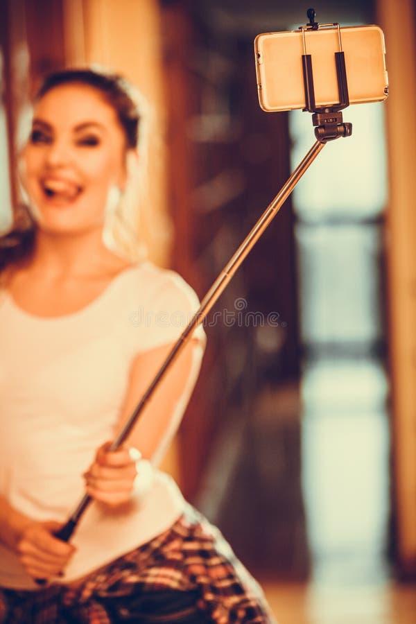 拍照片用selfie棍子的愉快的逗人喜爱的女孩 图库摄影