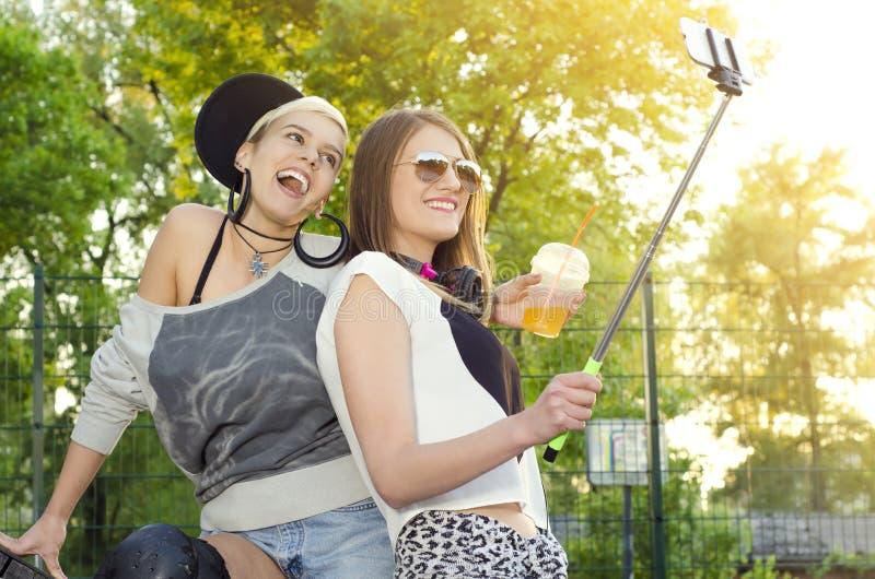 拍照片用selfie棍子的年轻时髦女孩户外 免版税库存图片