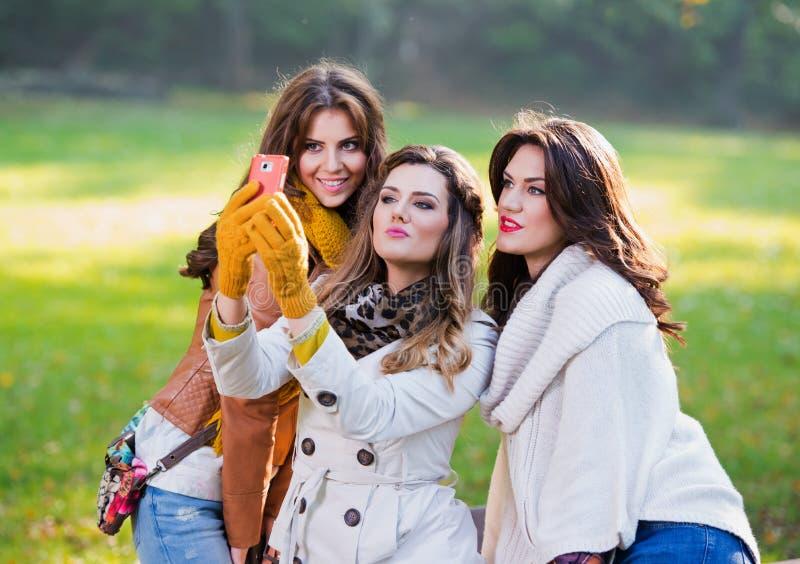 拍照片的三个美丽的少妇 免版税库存照片