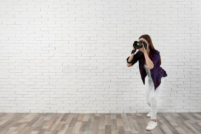 拍照片的专业摄影师在白色墙壁附近 r 免版税库存图片
