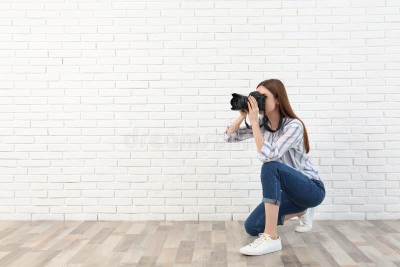 拍照片的专业摄影师在白色墙壁附近 r 库存图片