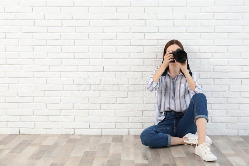 拍照片的专业摄影师在白色墙壁附近 r 免版税库存照片