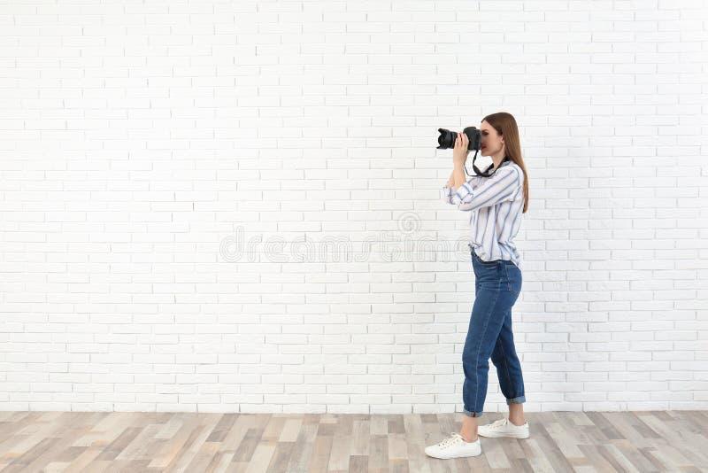 拍照片的专业摄影师在白色砖墙附近 库存照片