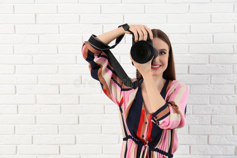 拍照片的专业摄影师在白色砖附近 免版税库存图片
