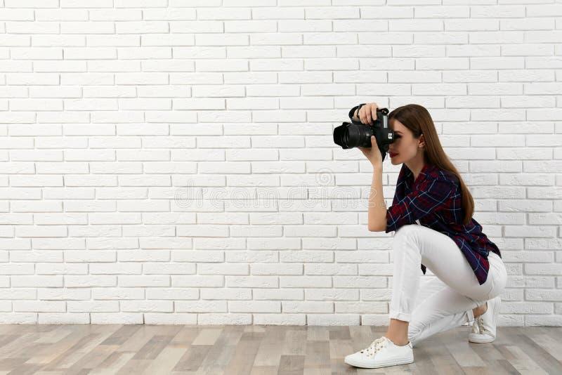 拍照片的专业摄影师在砖墙附近 r 库存照片