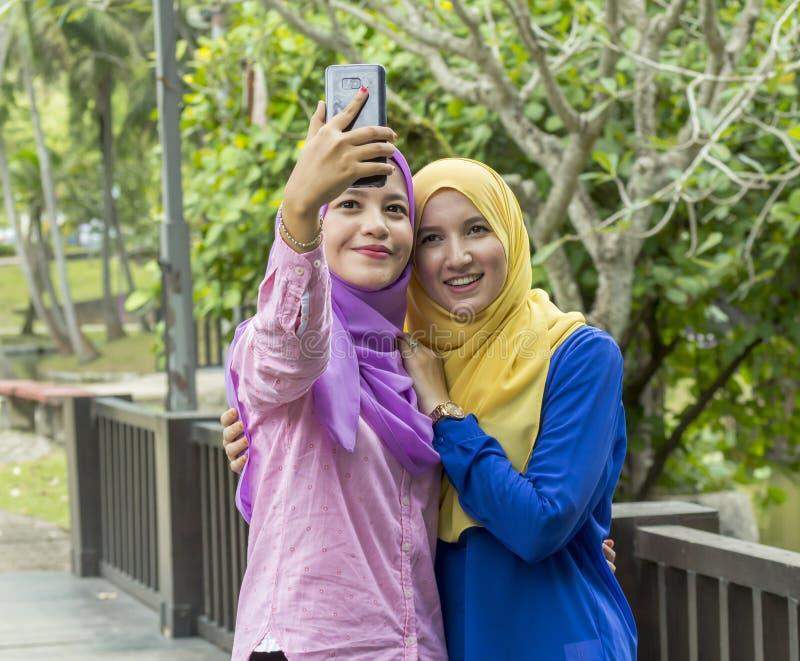 拍照片的两位大学生在公园 免版税库存照片